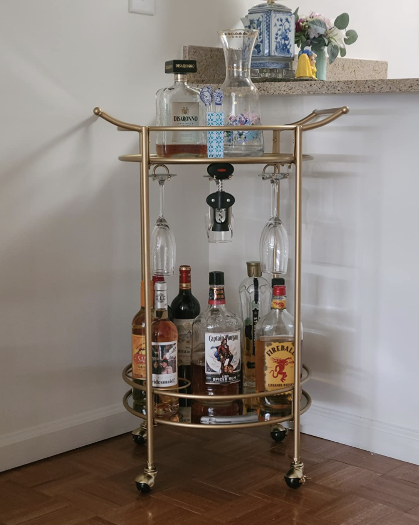 Reviewer's bar cart sits in the corner of a dining room and is holding various liquor bottles and barware