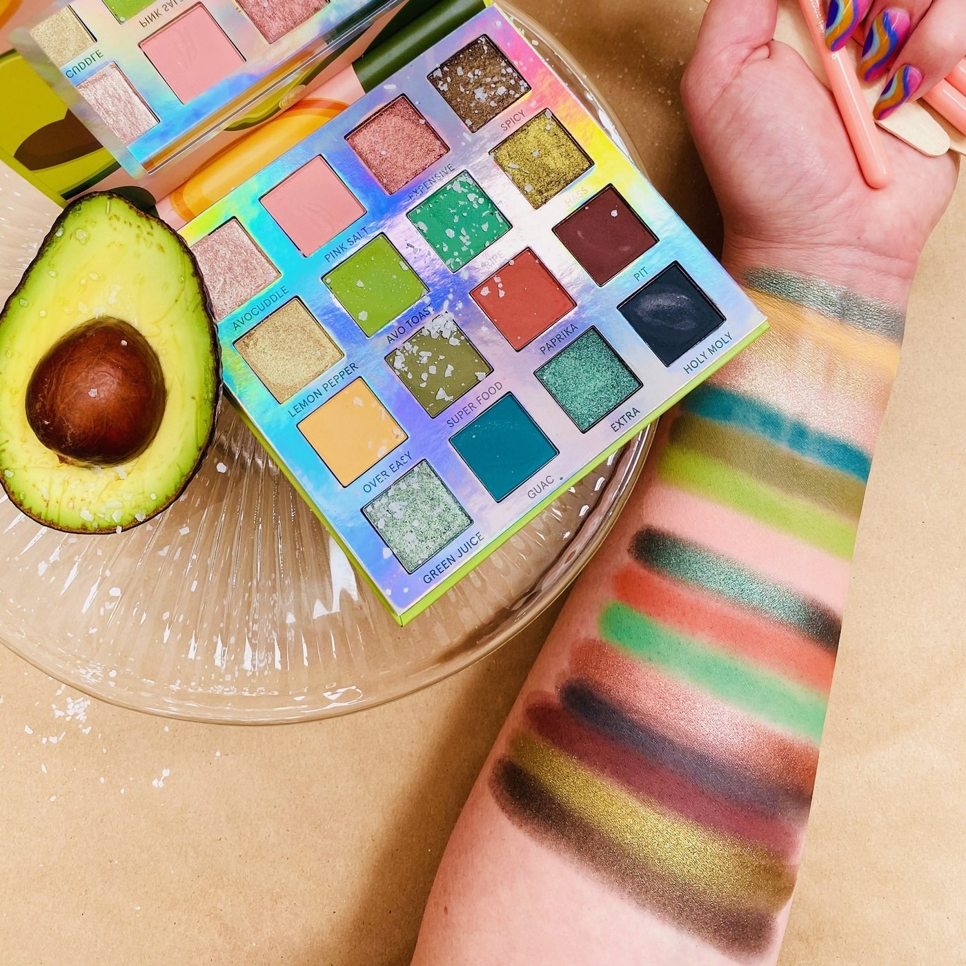 the palette with various yellow, green, and pink tones next to sliced avocado