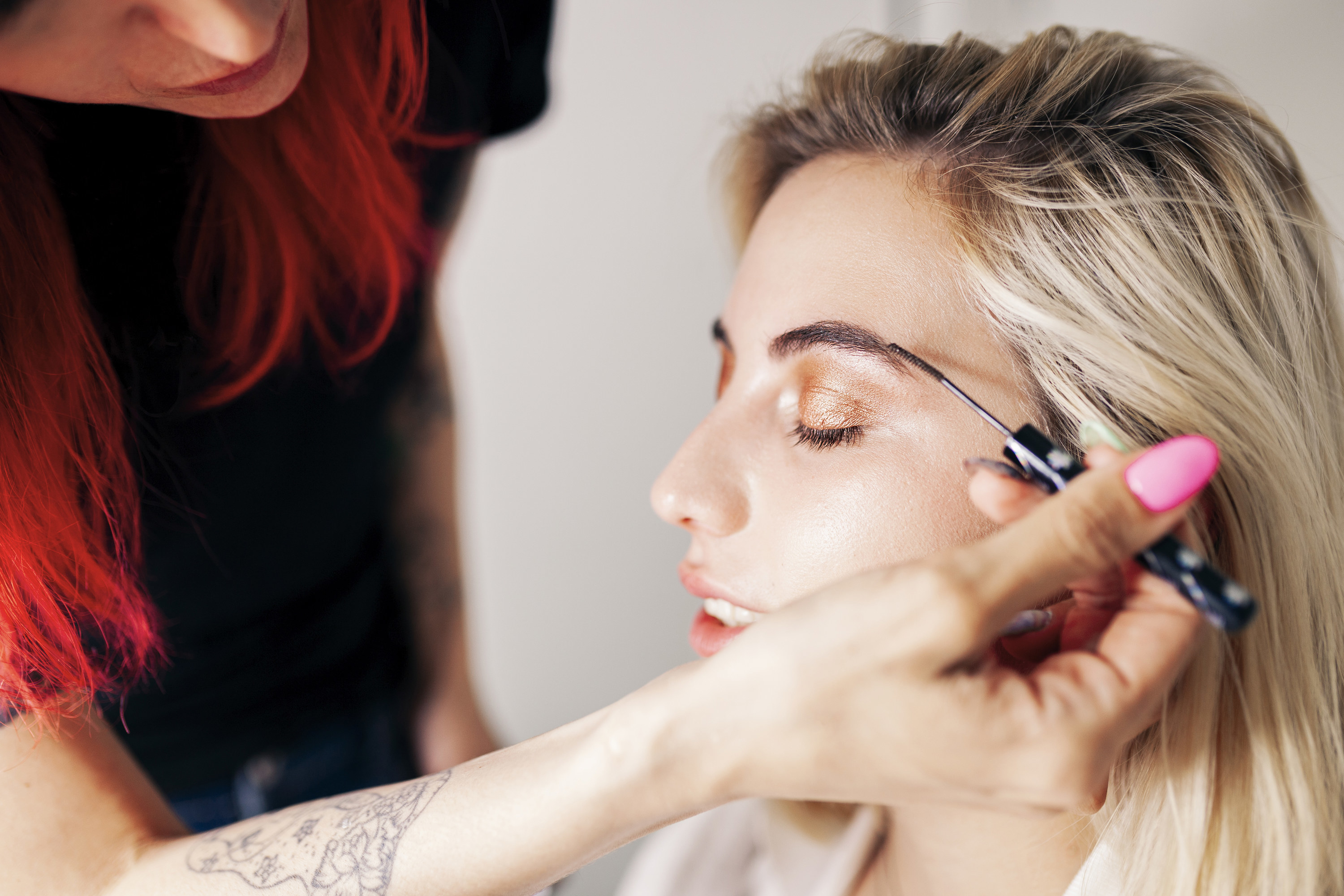 A person getting their eyebrows done by a makeup artist