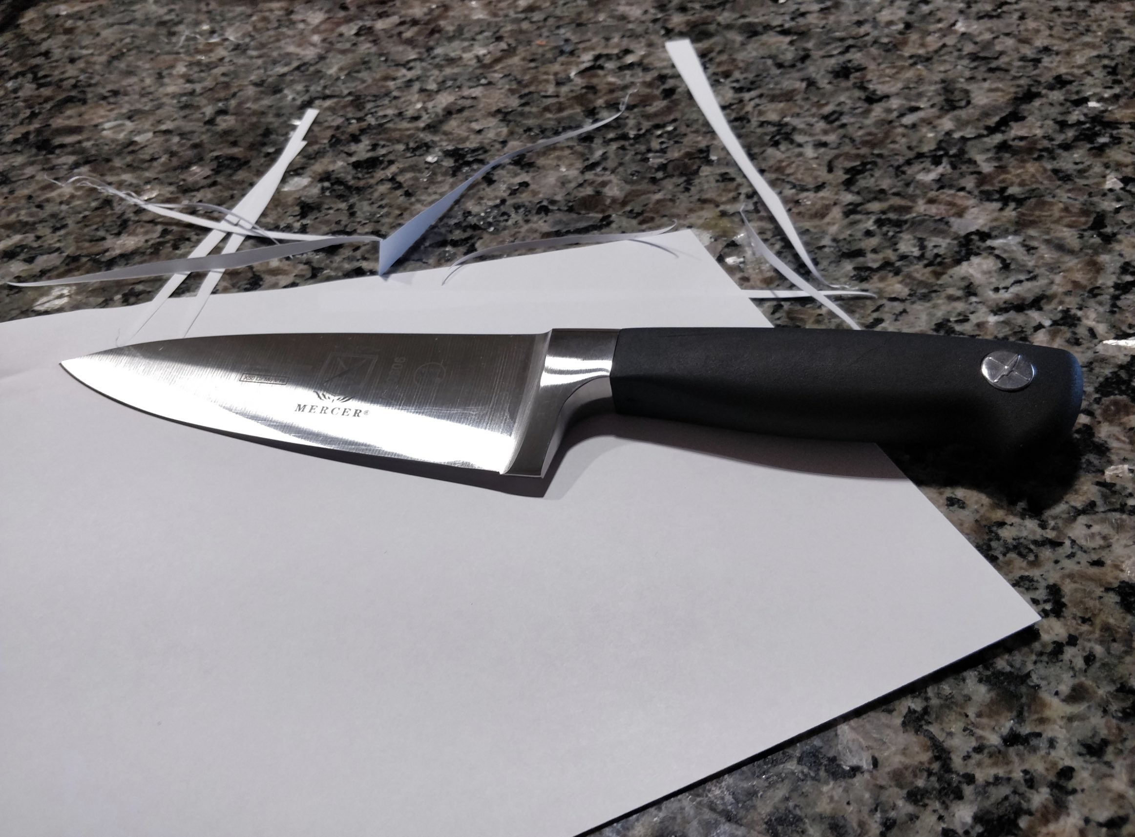 the chef's knife on top of a piece of paper that's been cut with the knife