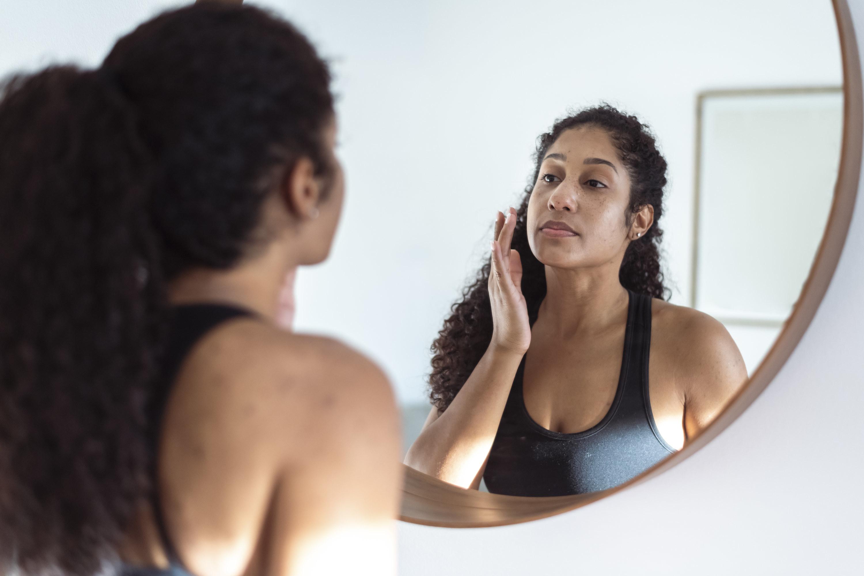 A person touching their cheek in the mirror