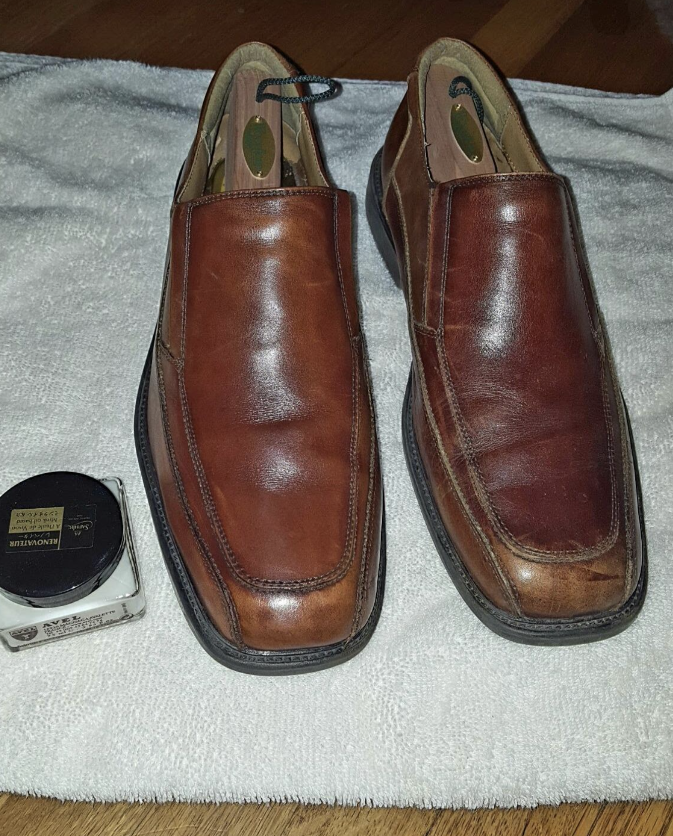 a jar of leather conditioner next to a pair of brown leather shoes, with the one on the left looking more vibrant and showing less scuffs than the right one after being treated with the conditioner