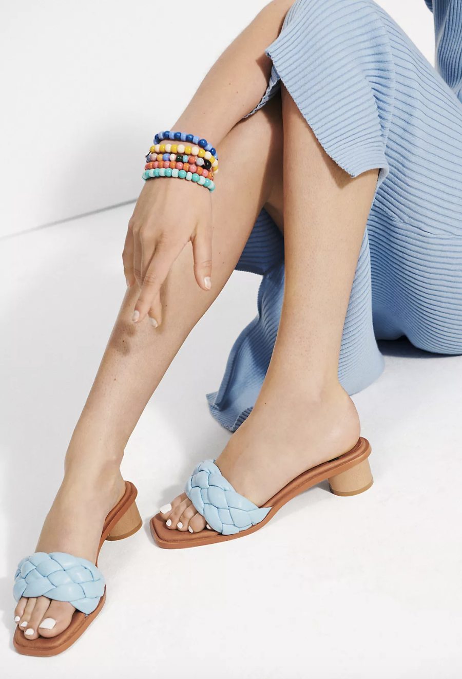 model wears wooden mules with puffy blue leather straps