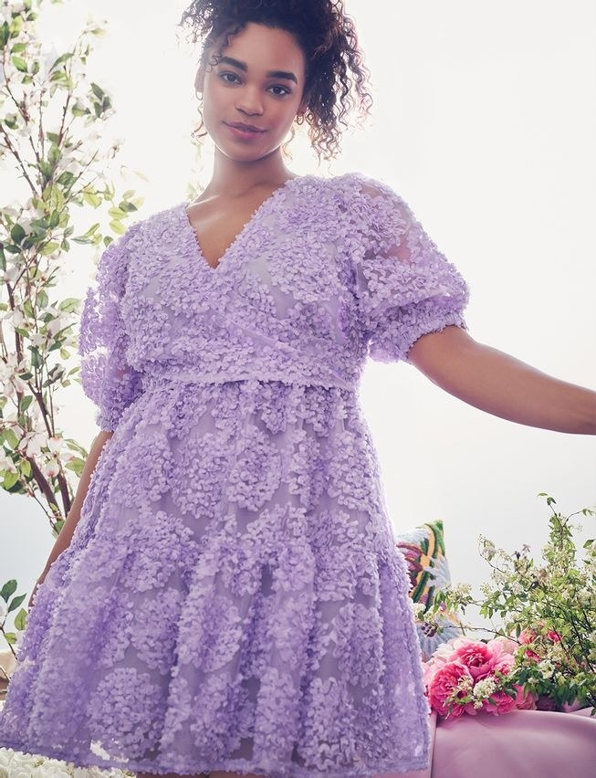 model wearing purple dress with bow tie in back and poofy sleeves