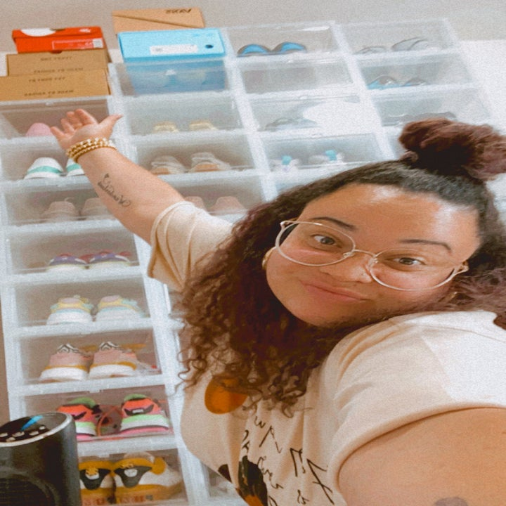 buzzfeed editor smiling and gesturing to her shoe wall