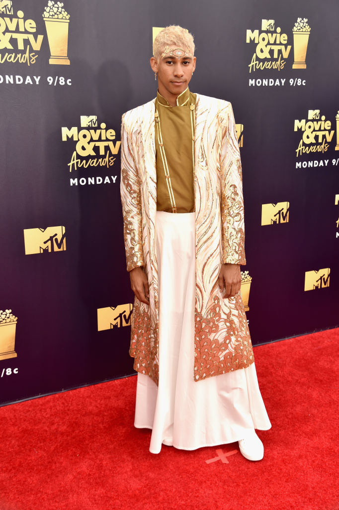 Keiynan Lonsdale at the 2018 MTV Awards red carpet; he is wearing a cream-coloured skirt, a camel-coloured top and a embroidered jacket of similar colours