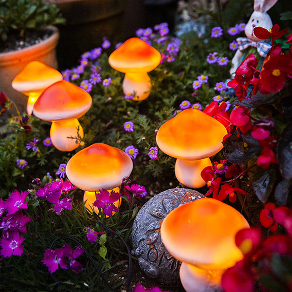 six of the mushroom-shaped solar lights glowing in a flower bed outdoors