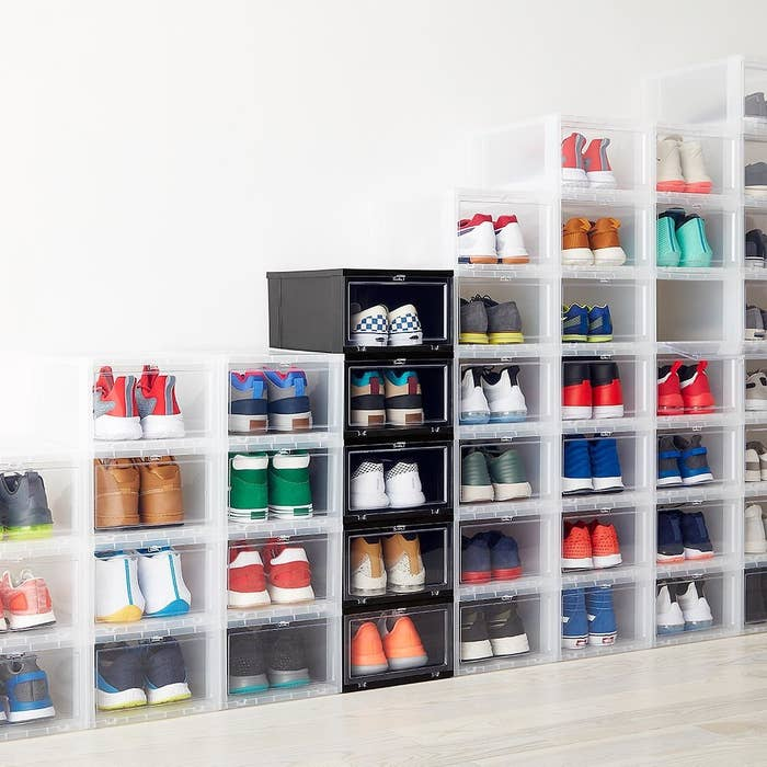 a bunch of the drop front shoe boxes with shoes in them stacked against a wall