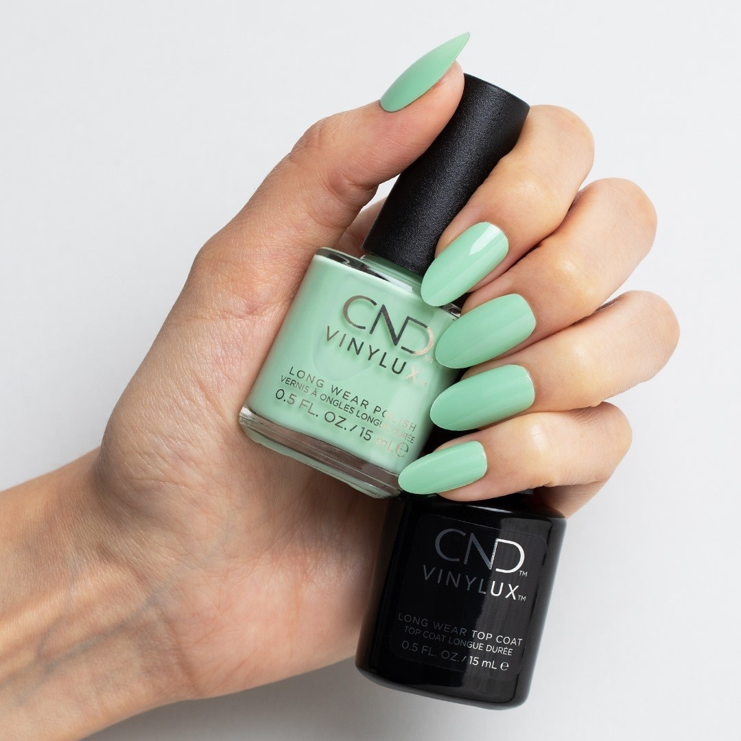 model hand holding cnd vinylux top coat and green polish