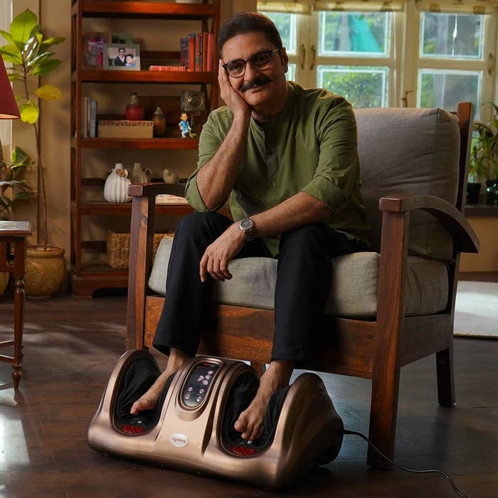 A man sitting on a chair with the foot massager