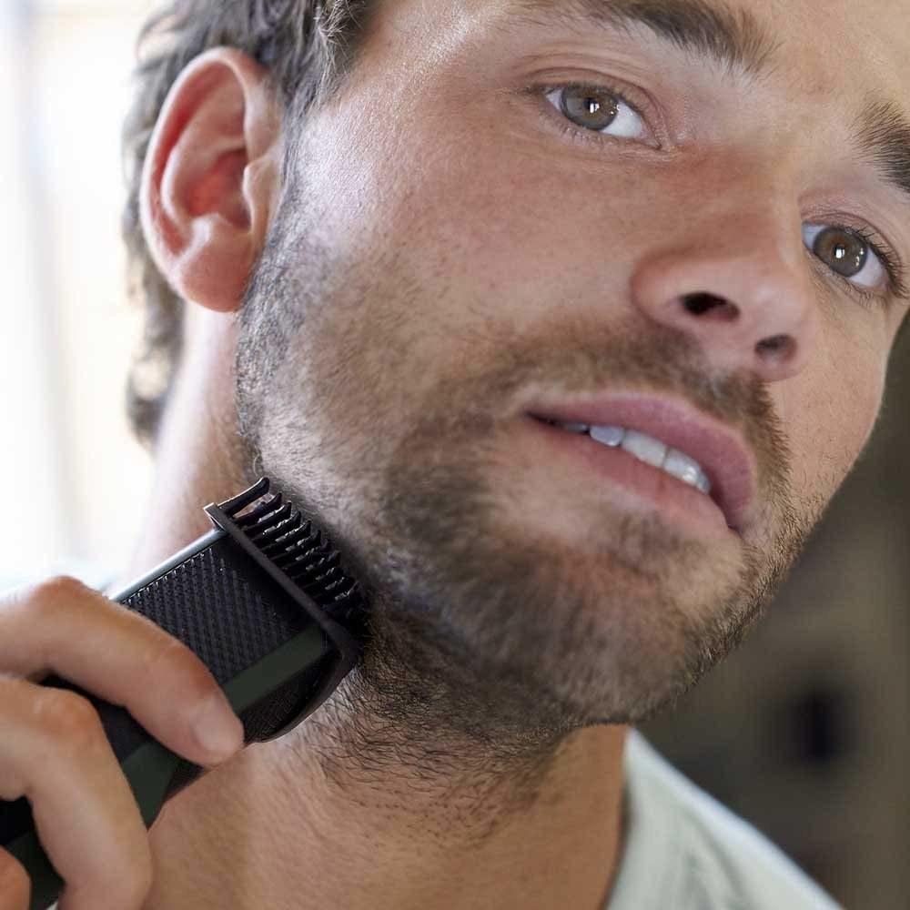 A man using the beard trimmer to trim his beard
