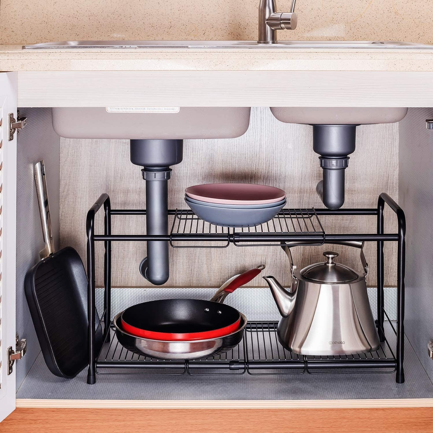 A metal rack organizing dishes in a cupboard underneath the sink