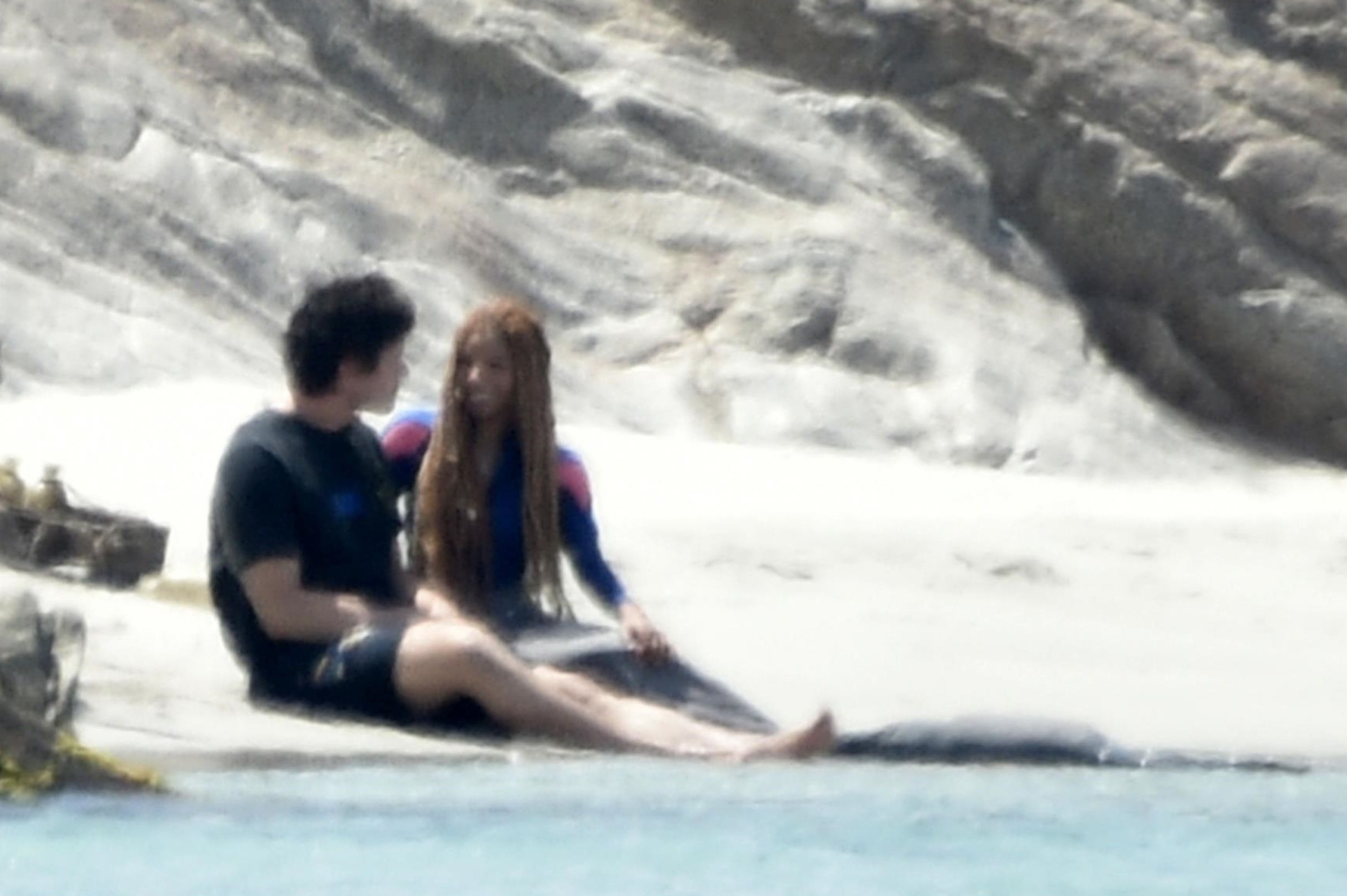 Jonah and Halle sitting near the water and looking at each other