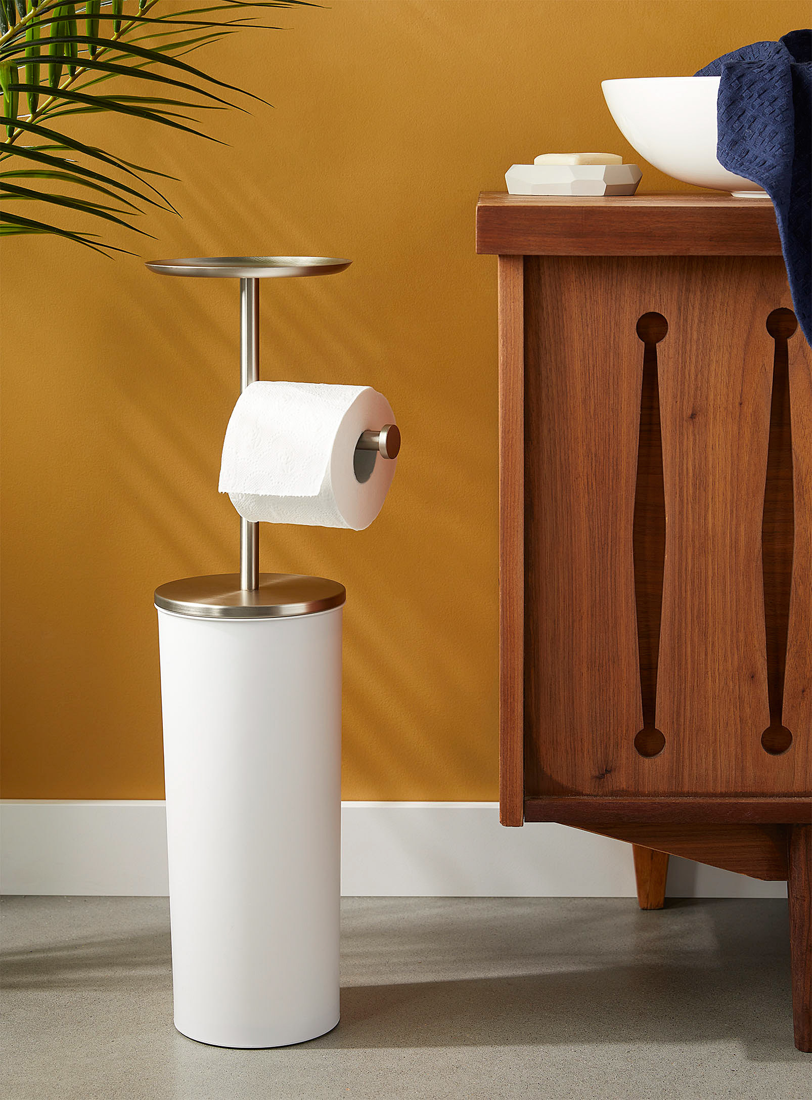 A toilet paper stand with a little tray attached to the top