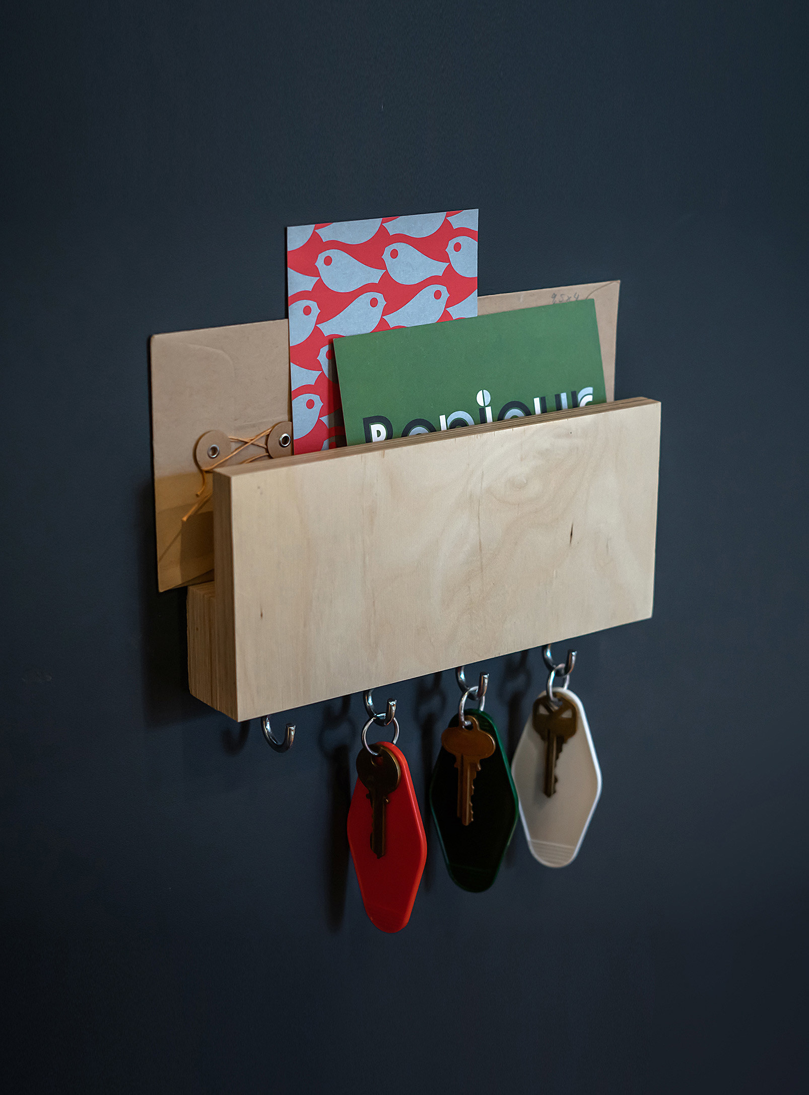 A small wooden shelf with letters stored at the top and keys hanging from four hooks on the bottom