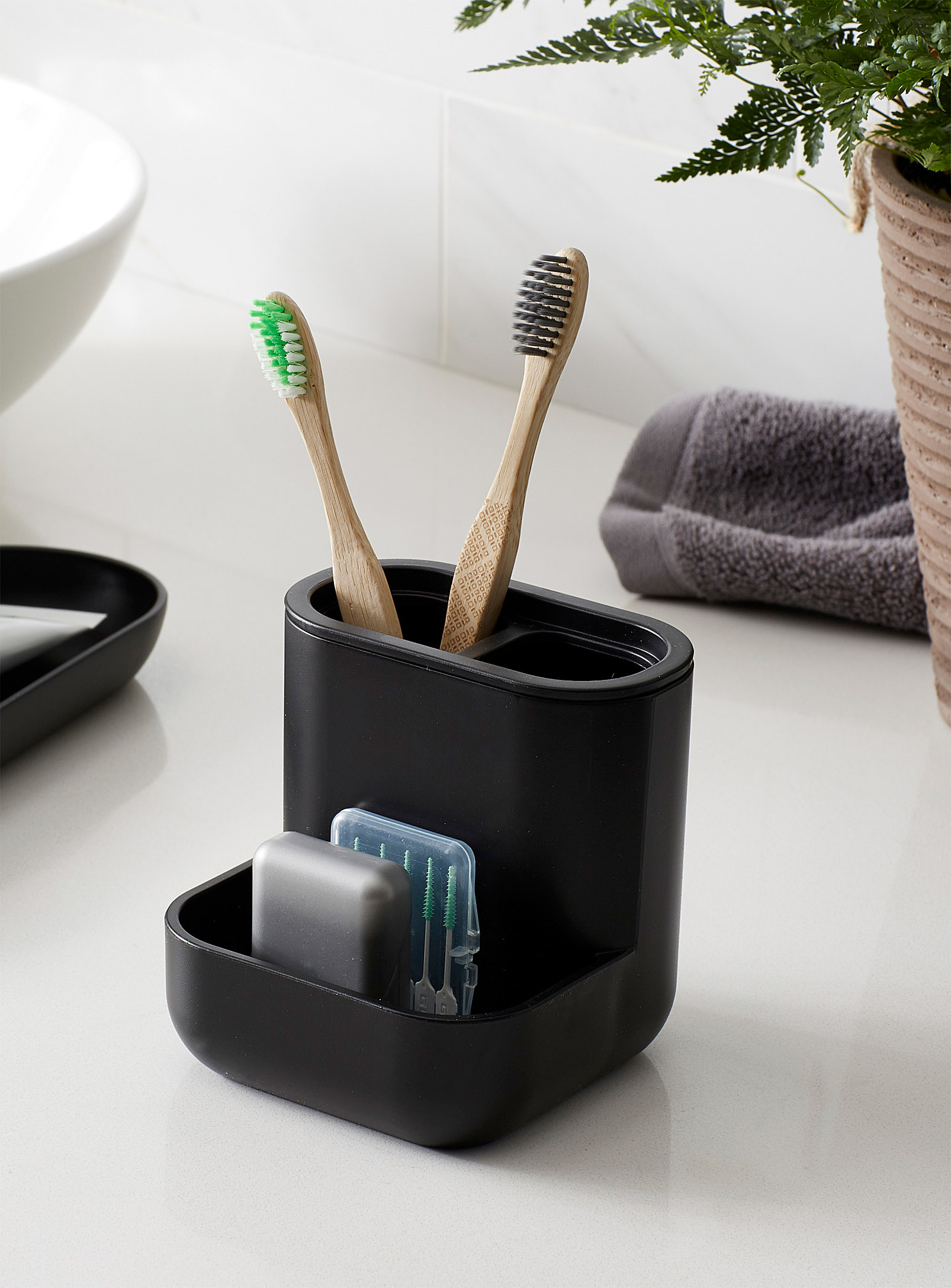 A plastic toothbrush holder with two toothbrushes in it