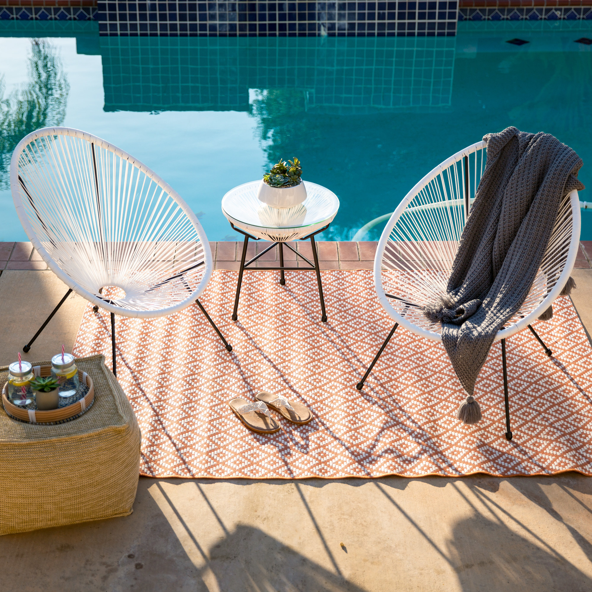 two round metal patio chairs with side table
