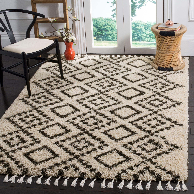 white rug and black geometric design and tassels