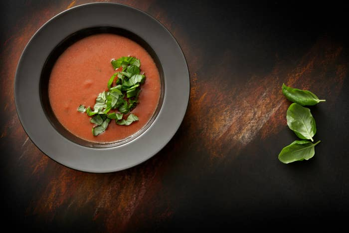 A bowl of tomato soup with basil.