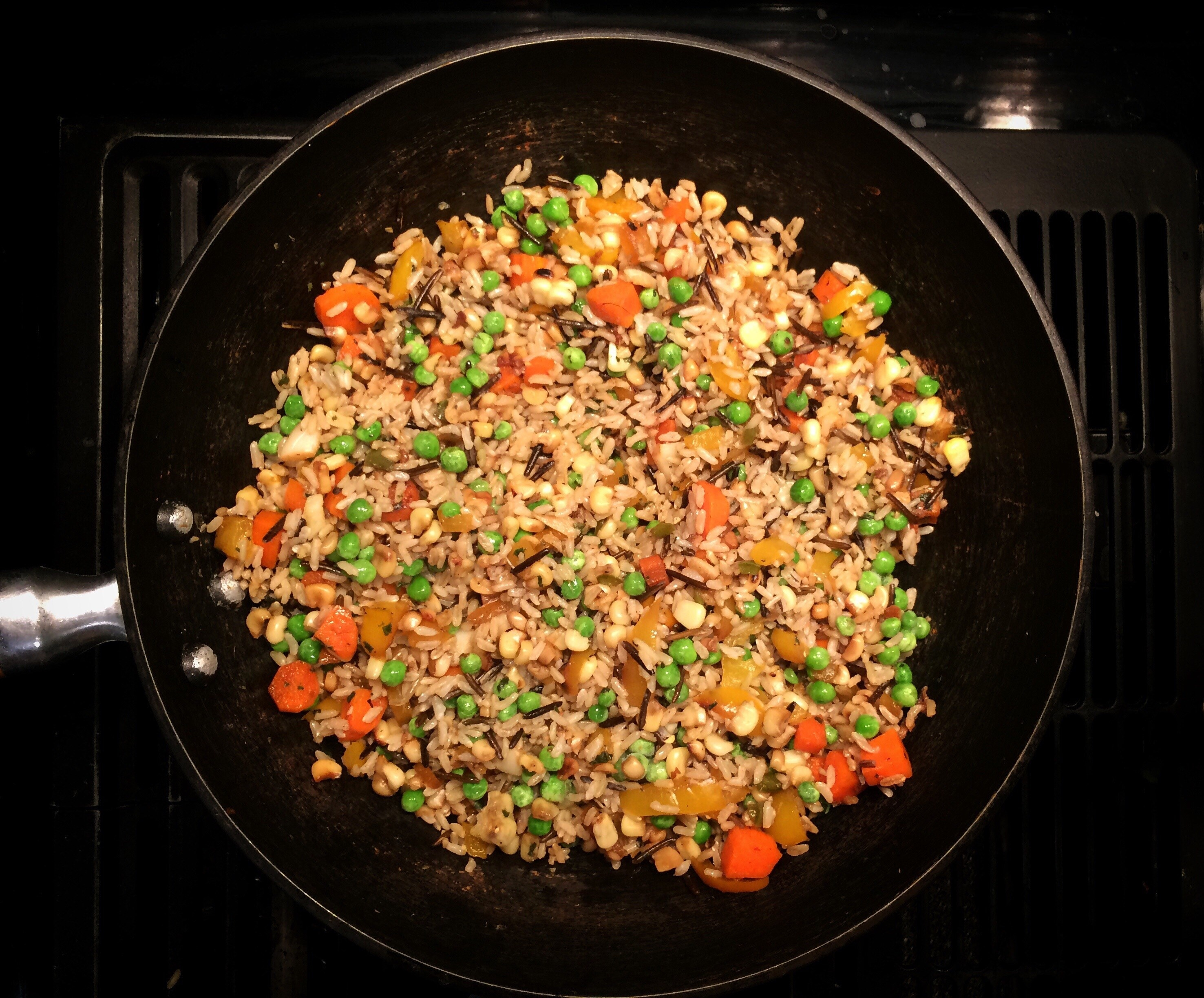A skillet of fried rice with peas and carrots.