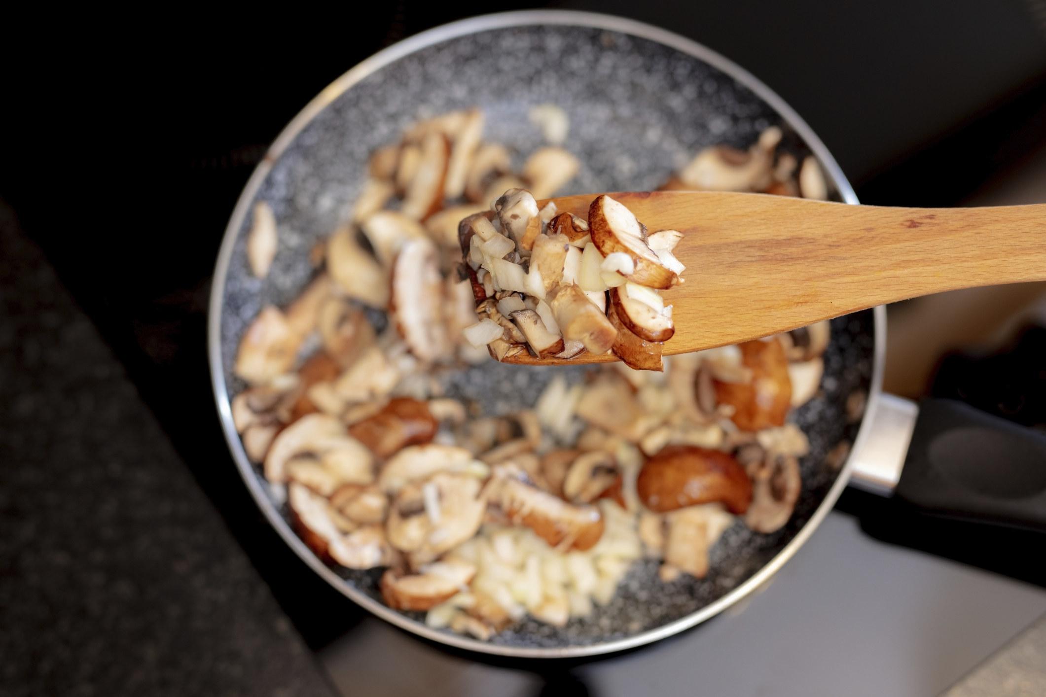Stirring mushrooms in a sauté pan.