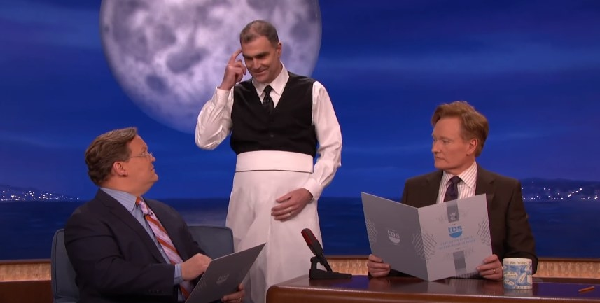 Conan and Andy Richter ordering food on set and a waiter listening