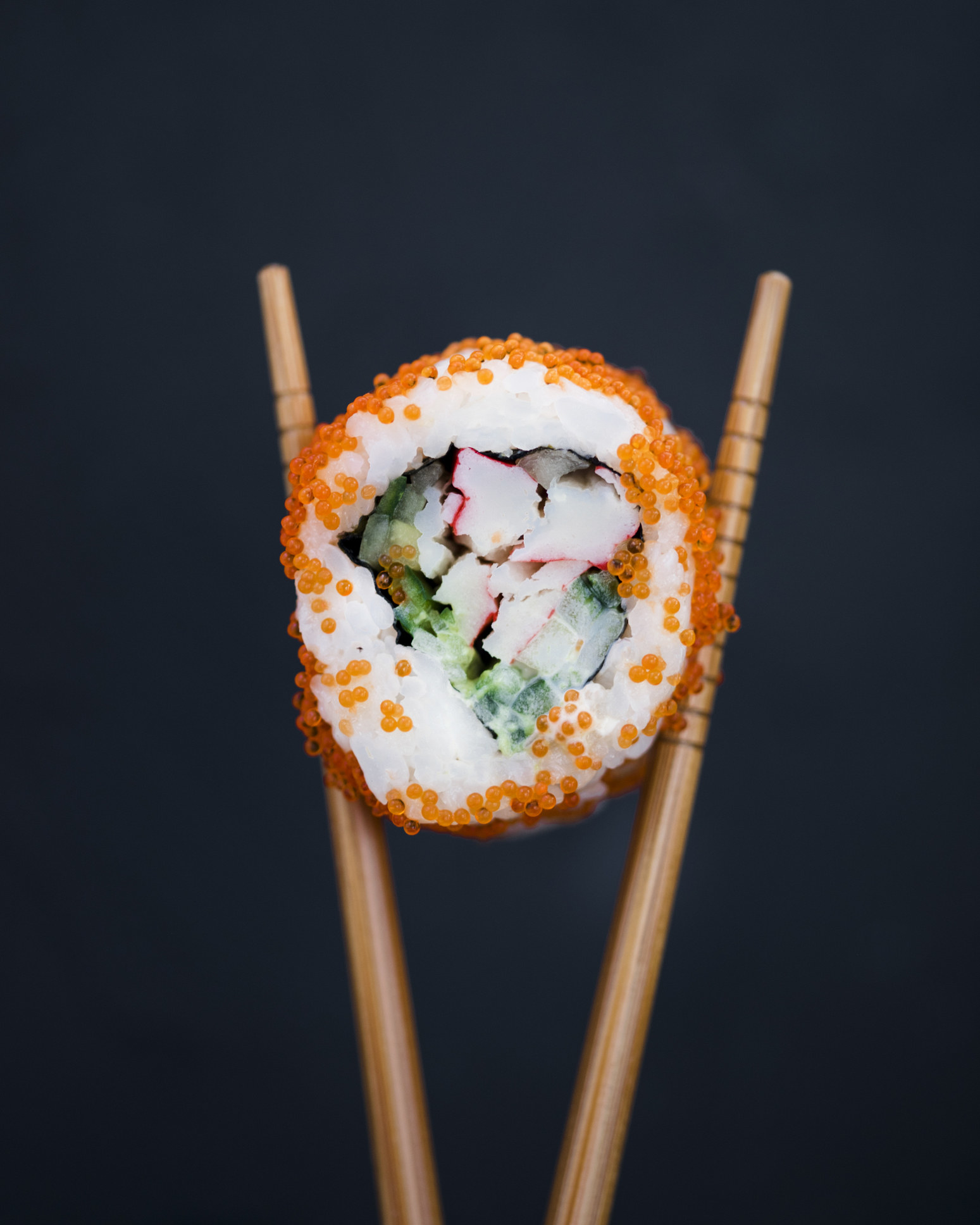 Someone holding a piece of sushi between chopsticks.