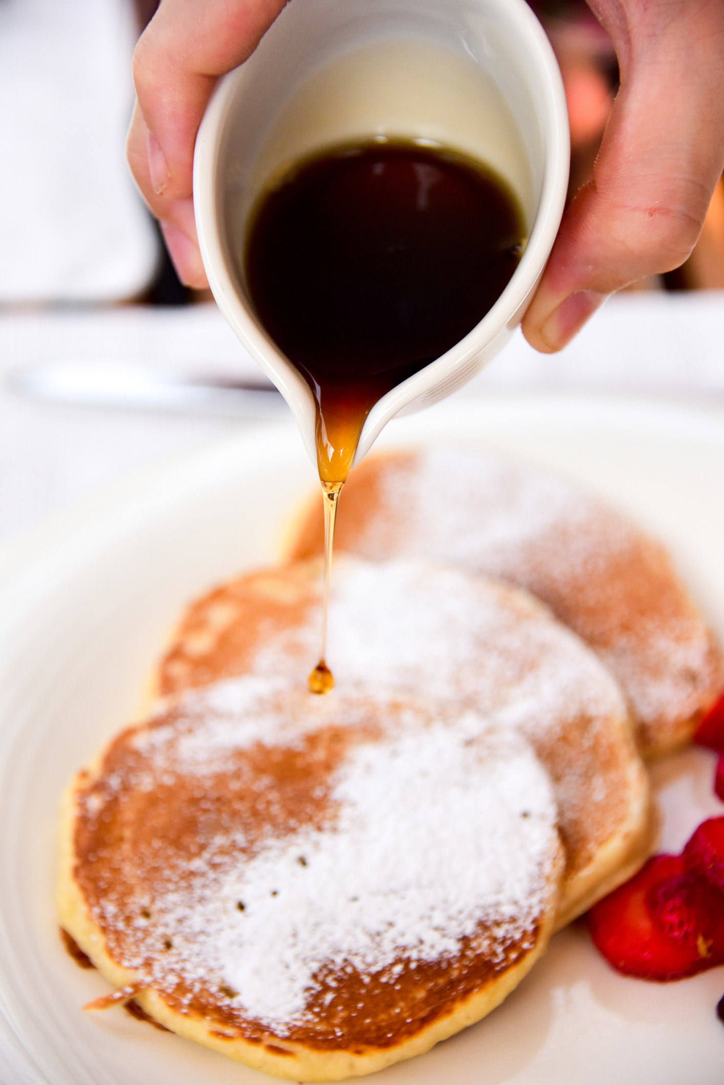 Pouring syrup onto pancakes.