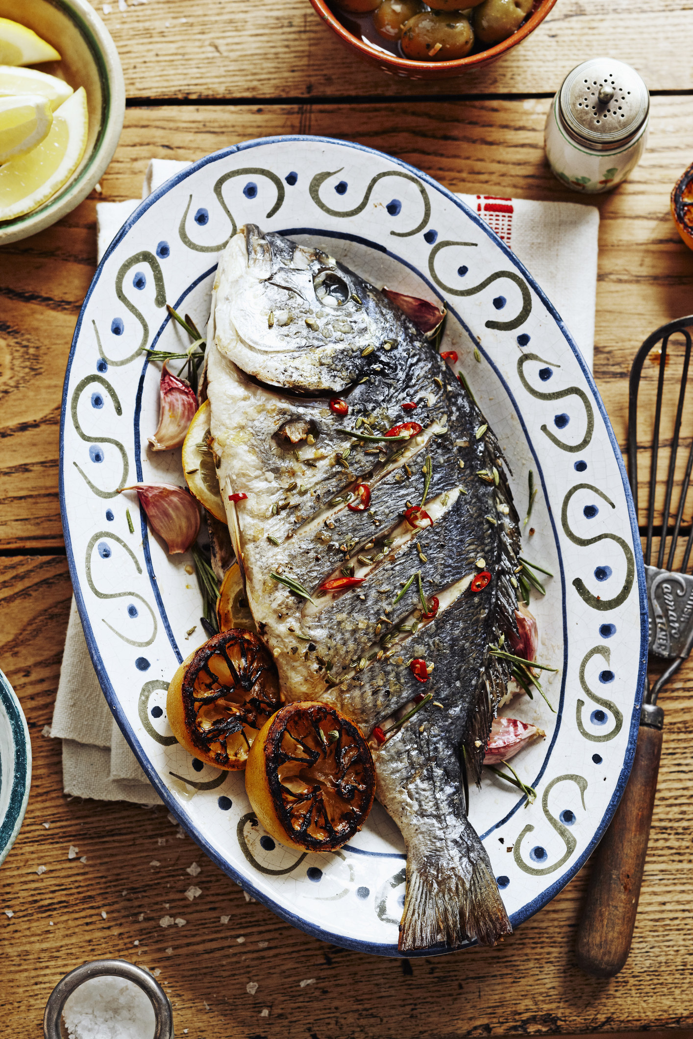 A whole roasted fish on a plate.