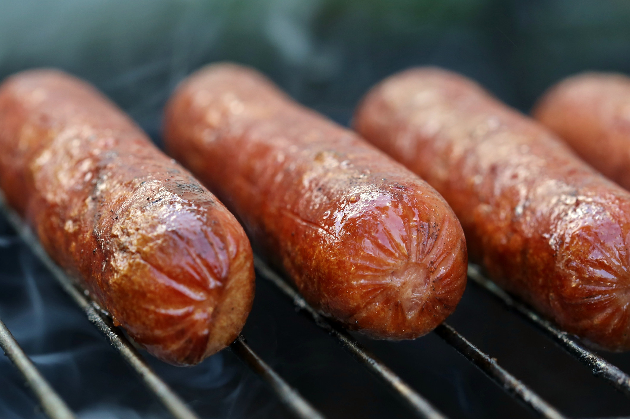 Hot dogs cooking on the grill.