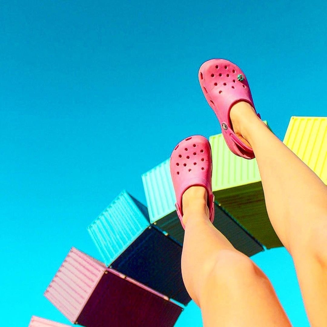 A person lifting their legs toward the sky showing off their crocs