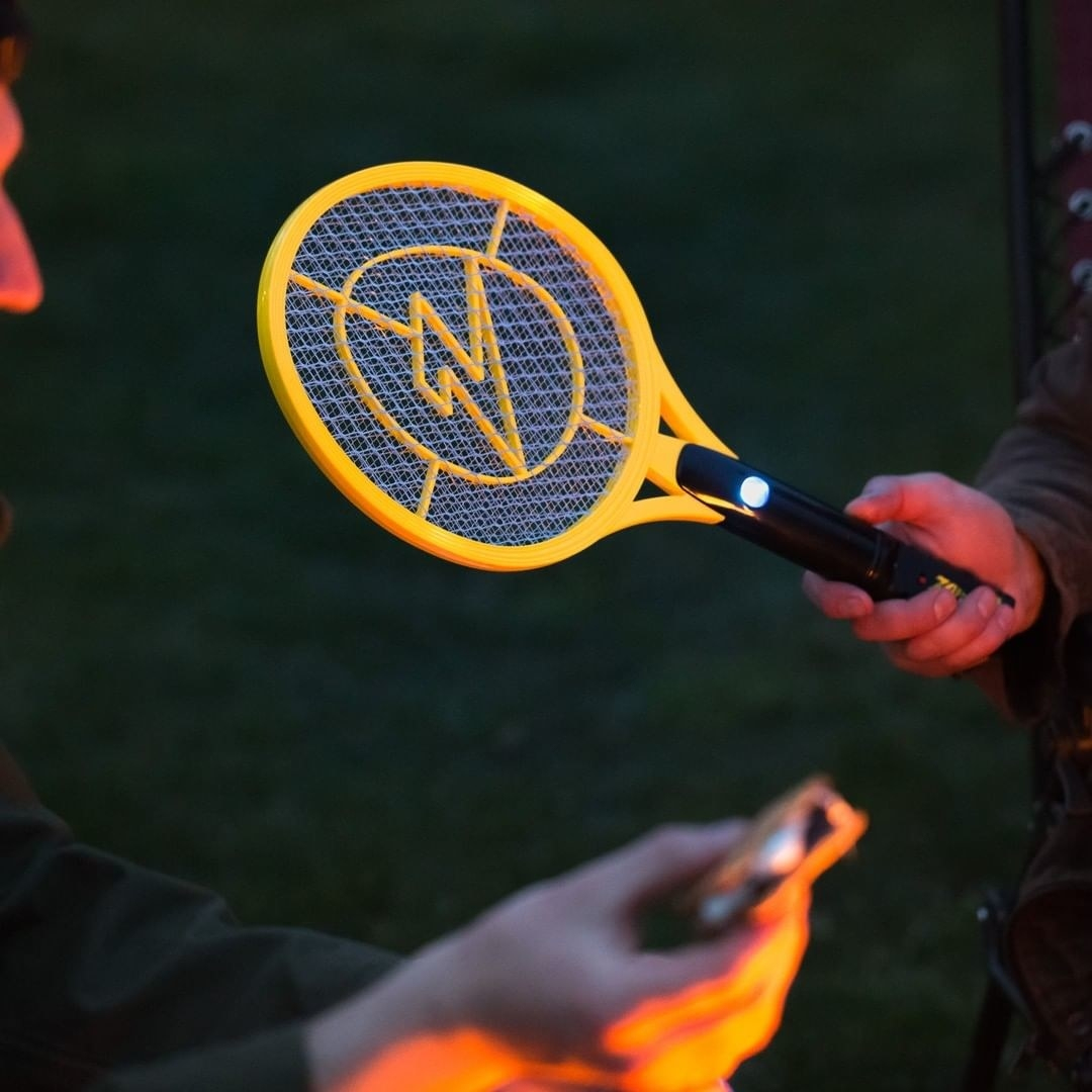 A person holding one of the electrified bug-zapping rackets