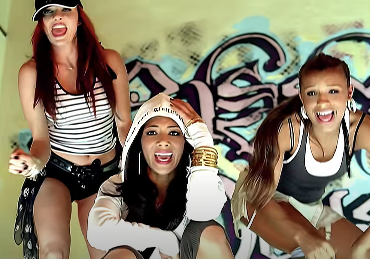 the Pussycat dolls singing in front of a graffiti wall