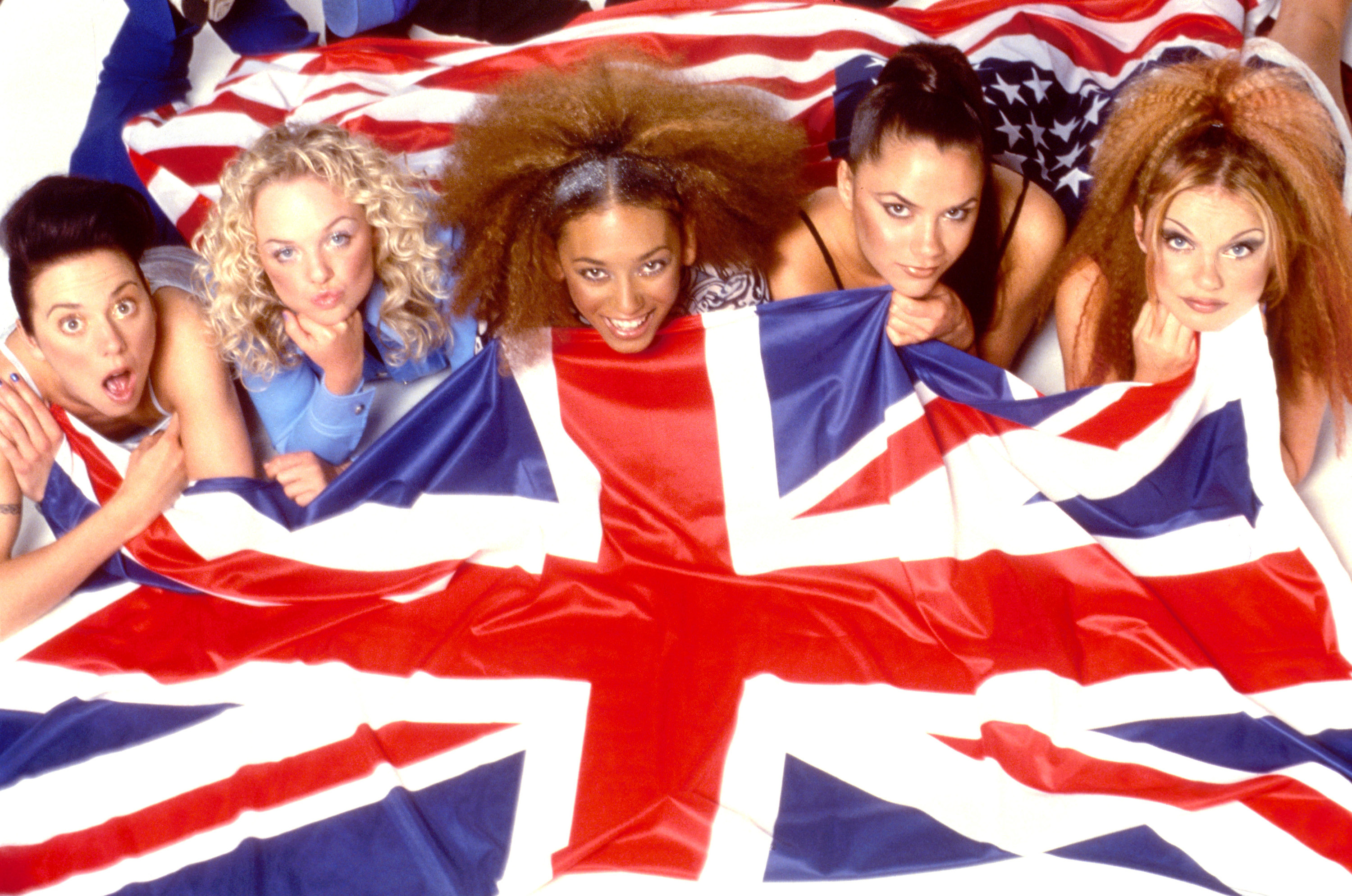 The Spice Girls pose with a United Kingdom flag in 1997