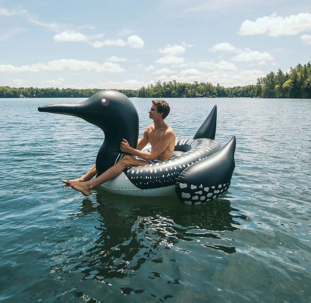 a person sitting on a loon-shaped float in a lake