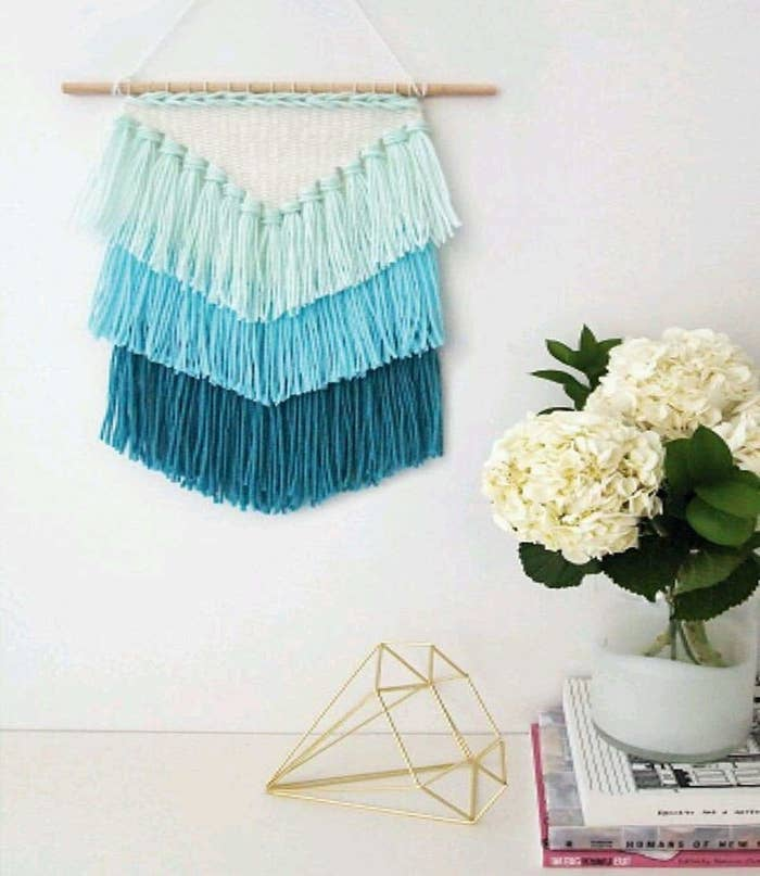 A tassel macrame wall hanging in 3 different shades of blue.