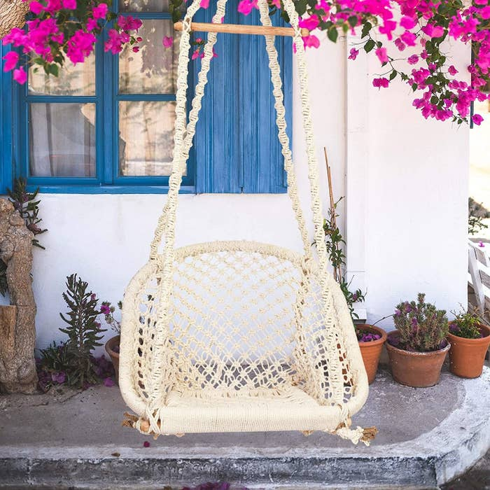 A macrame swing hanging outside a white house with blue windows.