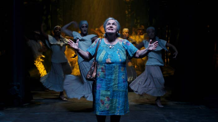 Abuela Claudia with her arms raised as she looks to the sky