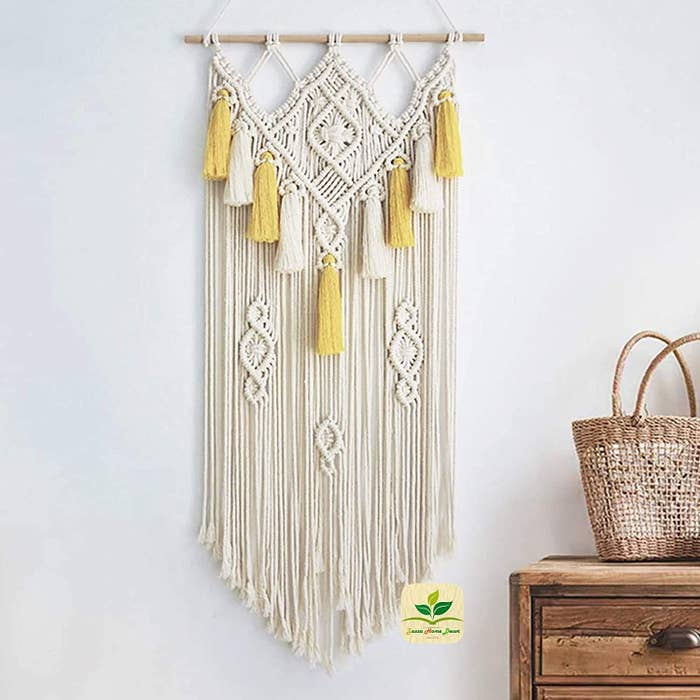 A Beige and yellow macrame wall hanging.