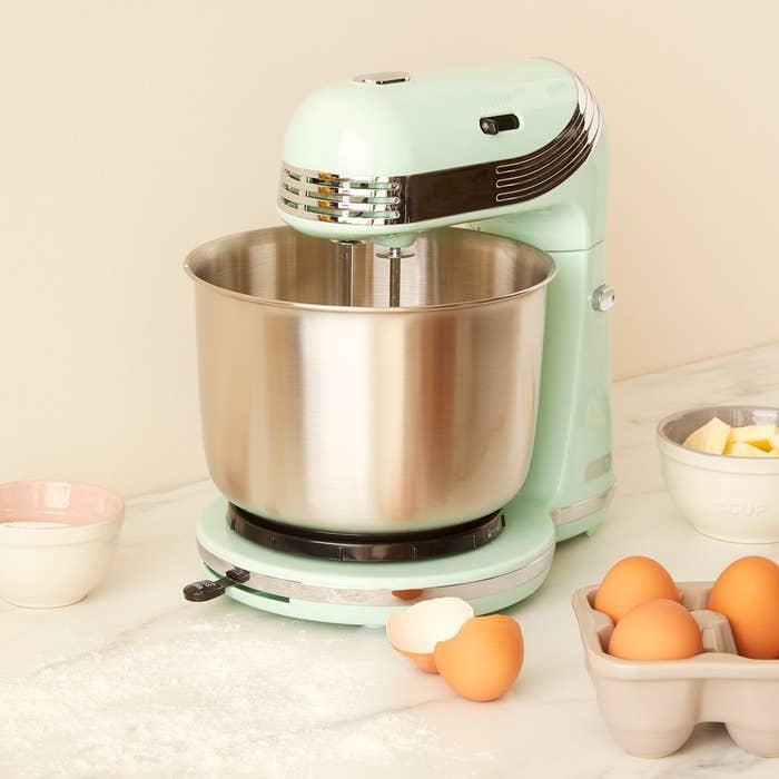 The mixer on a counter with eggs, butter, and sugar surrounding it