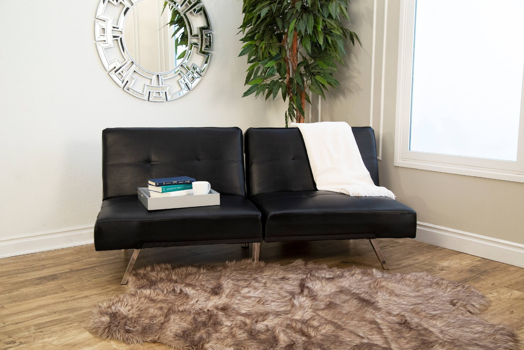 The black leather sofa with no arms, a slightly tufted back, and chrome legs