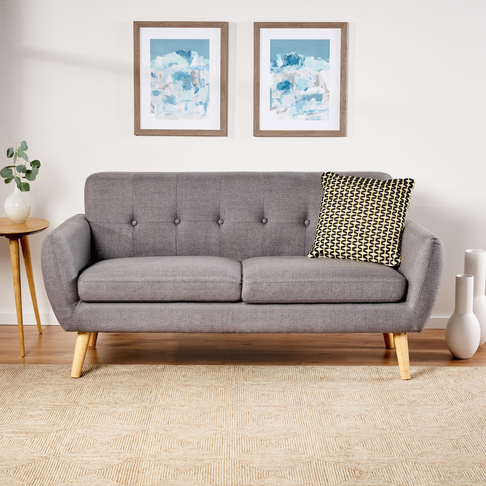 The gray sofa with button tufting on the back and light wooden legs