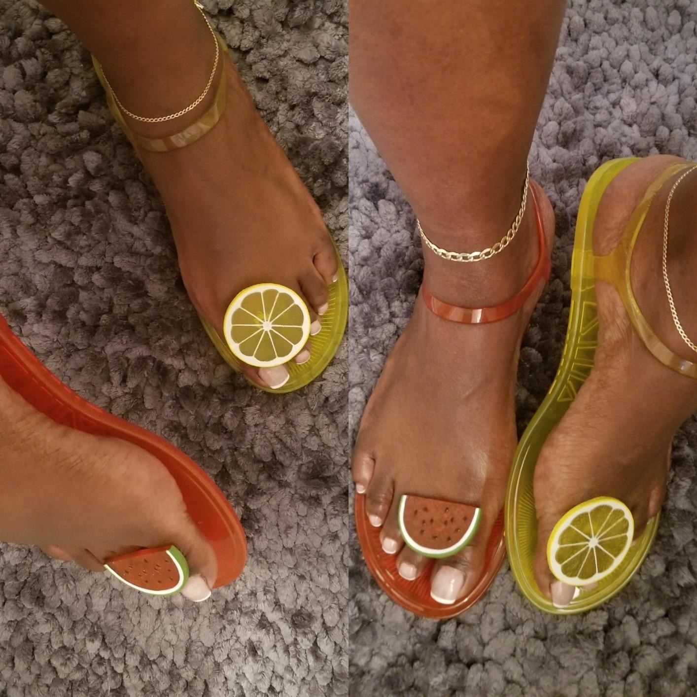 A reviewer models the sandals in the lemon and watermelon styles