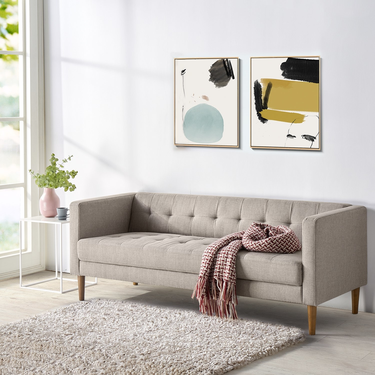 The low oatmeal-colored couch with button-tufting on the seat and back cushion as well as wooden legs