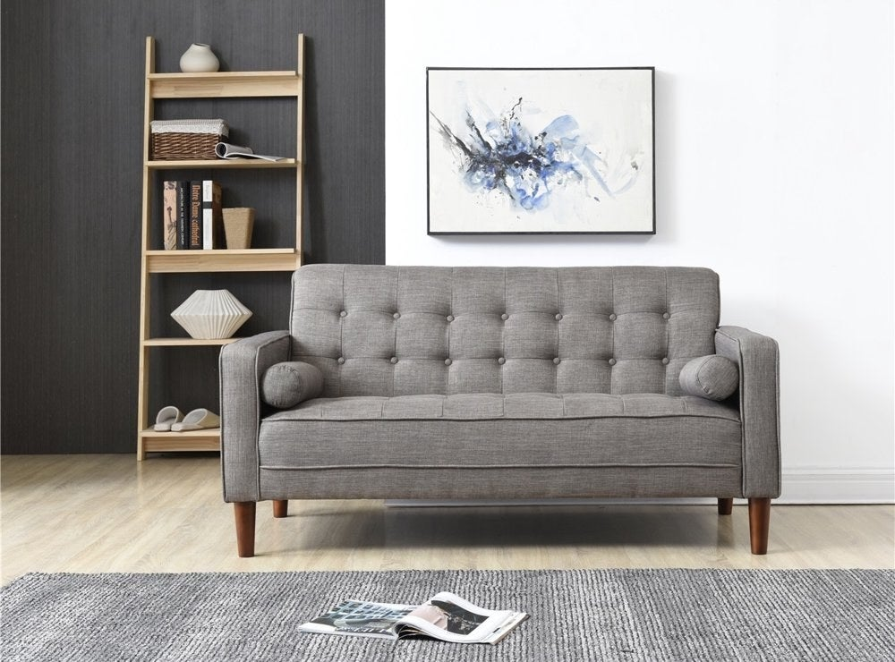 The gray sofa with a button-tufted back cushion and seat cushion, and wooden legs, in a living room