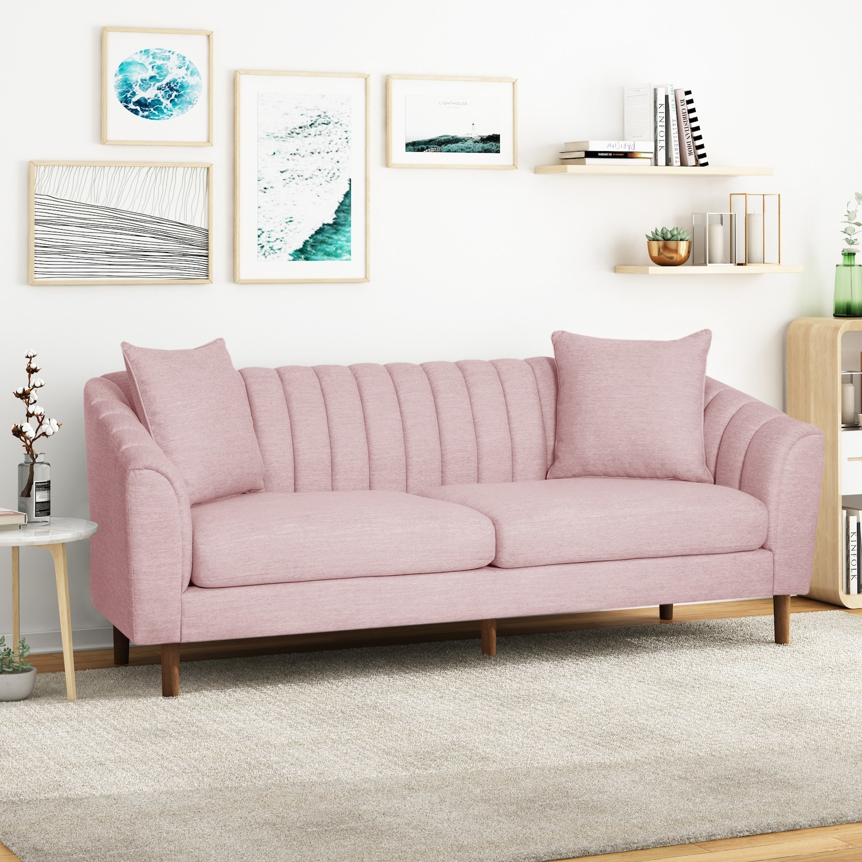 The pink couch with, vertical channel stitching on the back cushion, sloped arms, and two matching pillows
