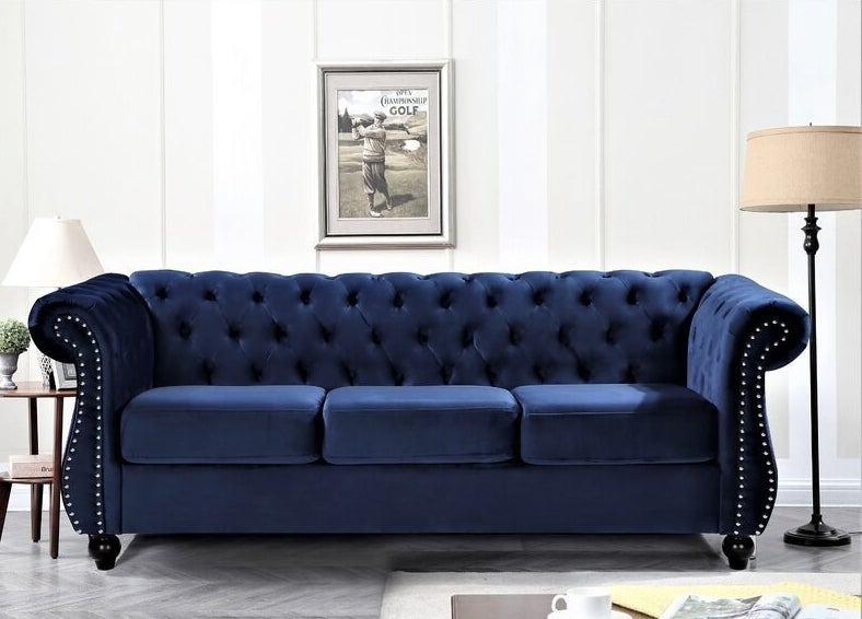The blue velvet Chesterfield couch with button tufting on the back and sides as well as nailhead accents on both arms