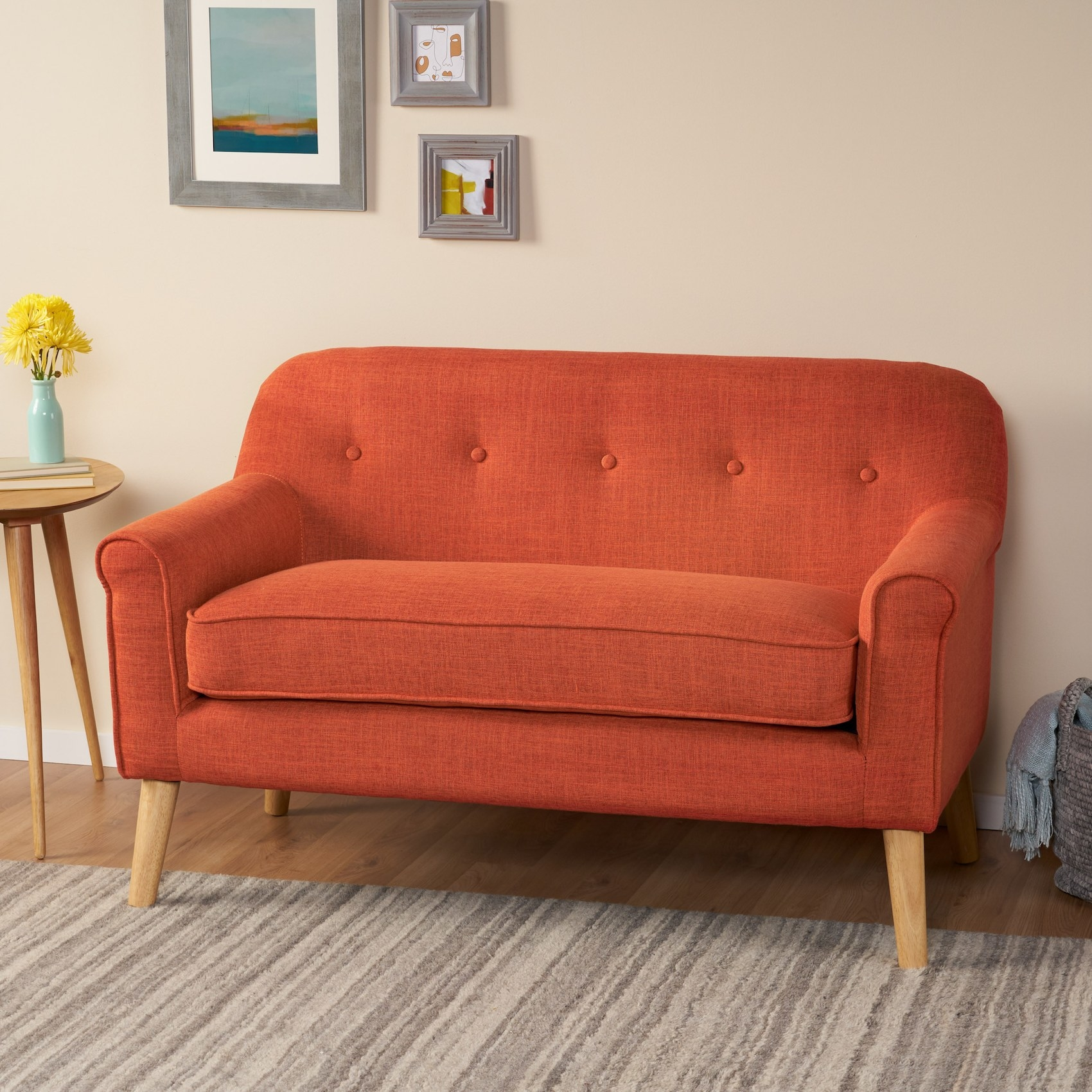 The orange loveseat with rounded arms and wooden legs in a living room