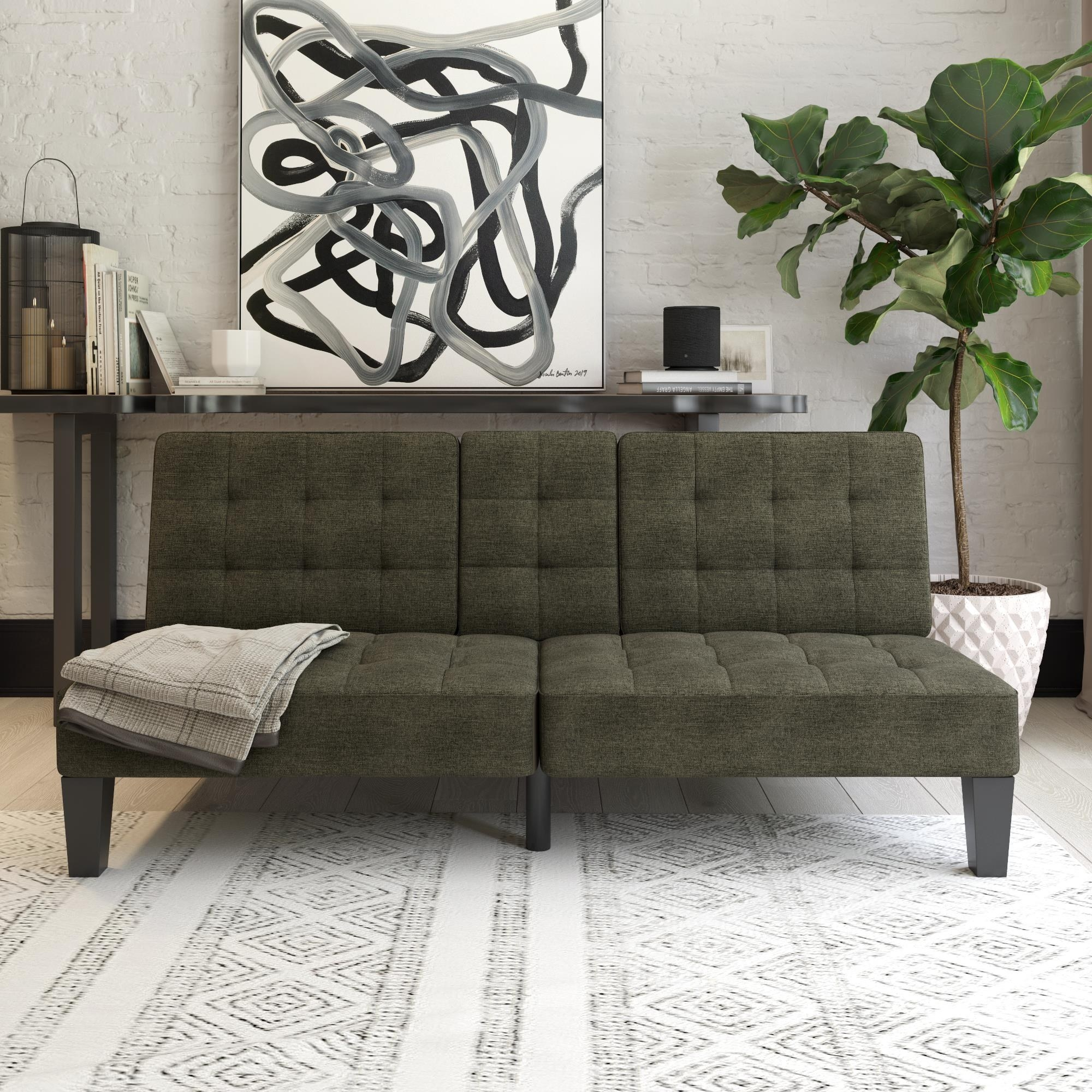 The army green couch with button tufting all over and a cupholder in the middle