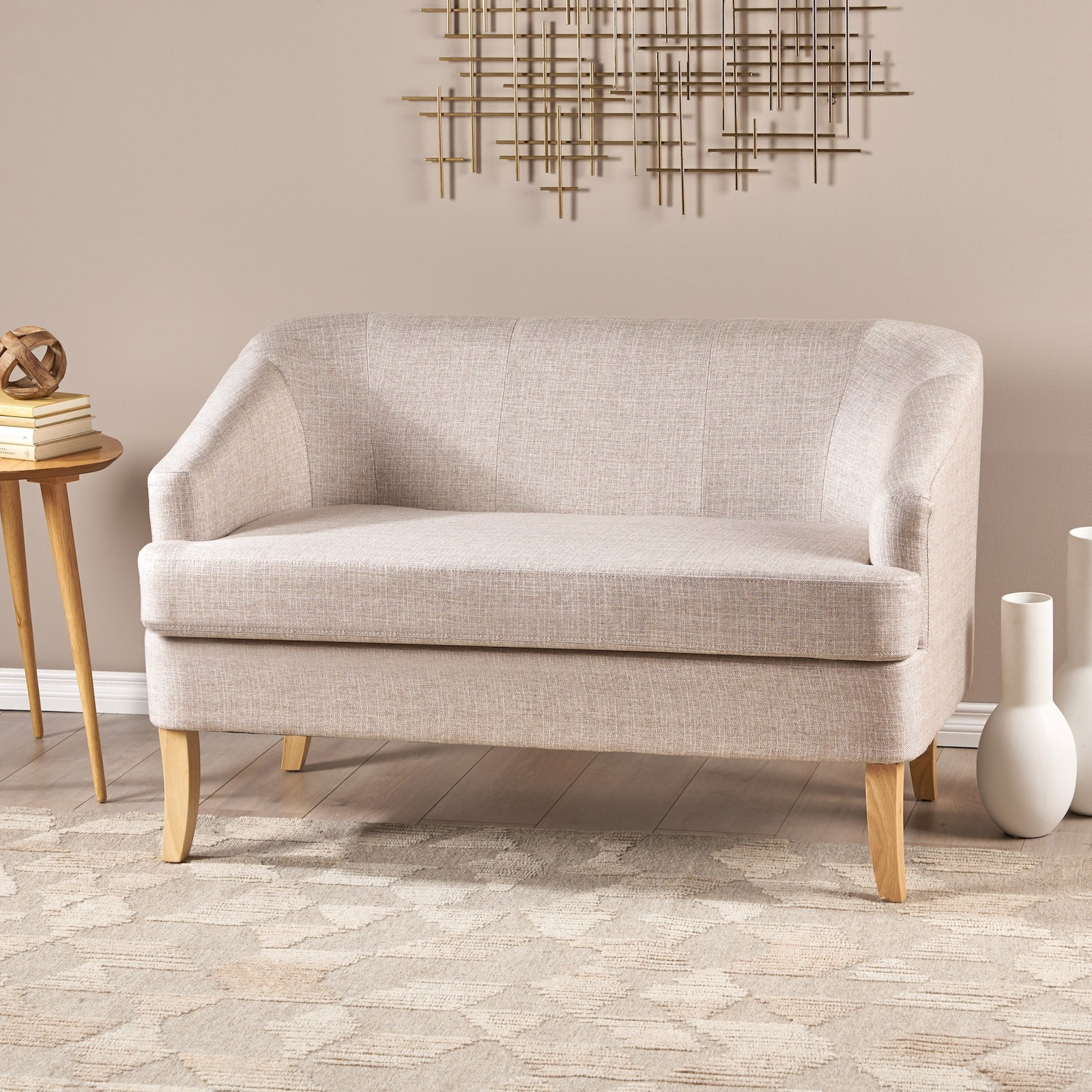 The beige couch with sloped arms and wooden legs in a living room